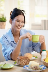 Cheerful young woman having breakfast