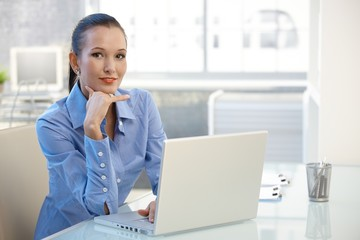 Portrait of young businesswoman with computer