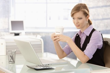 Young businesswoman drinking coffee at desk