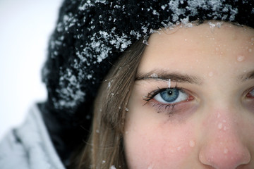 Closeup photo of little girl face in snow, half
