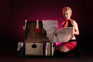 Junge Frau packt Koffer mit Wäsche aus