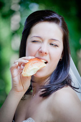 Bride portrait eating a patty in sunny park