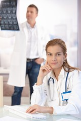 Attractive female doctor working on computer