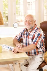 Portrait of elderly man in study at home