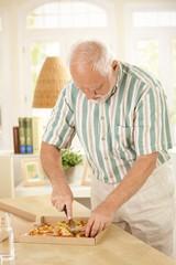 Elderly man slicing up pizza.