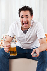 young boy watching the television and holding a glass of beer
