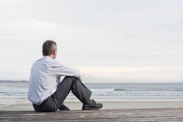 Nachdenklicher Geschäftsmann sitzt an einem Strand