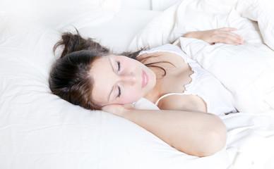 frau schläft im weißen kissen und bett