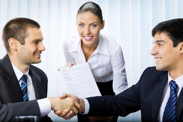Three businesspeople handshaking with document at office