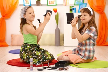 Two young girls playing with makeup