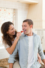 Lovers eating a strawberry in their kitchen
