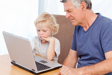 Lovely boy and his grandfather looking at their laptop