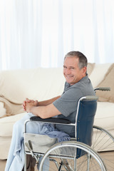 Mature man in his wheelchair looking at the camera