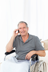 Senior in his wheelchair phoning