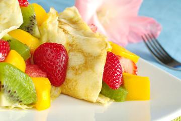 Crepes filled with fruits: strawberry, kiwi, mango, melon