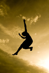 Wall Mural - freestyle gymnast silhouette in golden sky