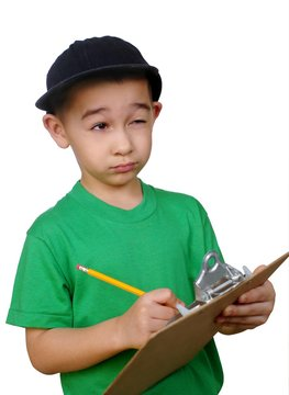 Boy writing on a clipboard tablet looking up thinking