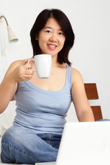 Asian woman having coffee while working on a laptop