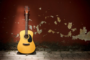 Acoustic guitar against grungy wall