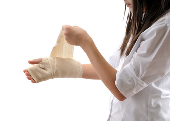Teen girl wrapping her hand with bandage isolated on white.