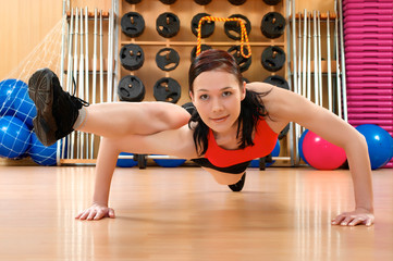 Young woman doing fitness exercises in a health club