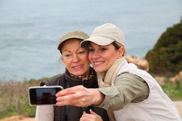 Women taking picture of themselves with telephone
