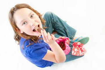 Young girl eating chocolate