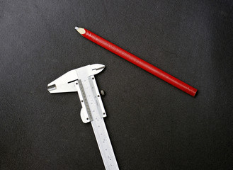 caliper and red pencil on back blackground