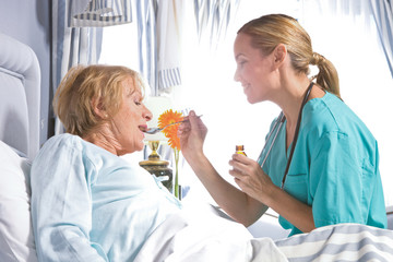 Nurse giving drugs to an old lady