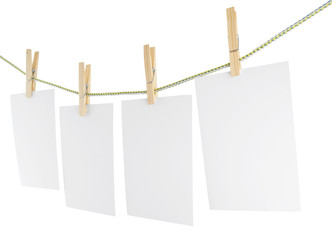 Blank pieces of paper and wooden clothespins isolated on white
