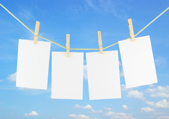 Blank pieces of paper and clothespins on sky background