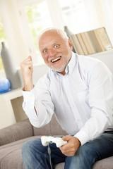 Senior man winning on computer game
