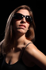 Beautiful young woman wearing dark sunglasses