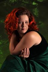 Porträt einer rothaarigen molligen Frau vor grünem Hintergrund
