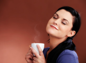 Woman with hot coffe and a rest of milk on her mouth