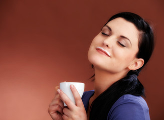Young woman with coffe and a rest of milk on her mouth