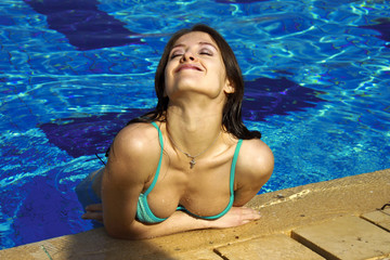 Injoying beautiful girl is having a rest in pool with smile