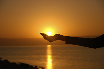 Hand holding the sun in the dead Sea