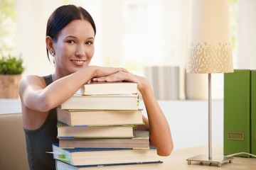 Girl posing with pile of books to learn
