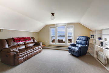 Top floor family room with brown leather sofa and blue chair