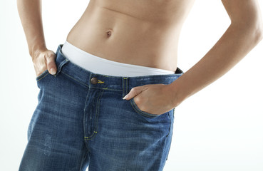 femme régime dans un pantalon jeans trop grand