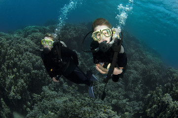 young boy scuba diver dives with mother