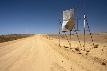 Photo sur Toile Desert de sable Broken billboard in desert