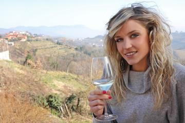 ragazza con vino bianco sulle colline