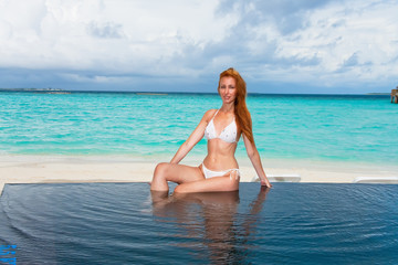 Young pretty woman in the pool and ocean in the background