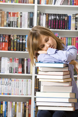 Young beautiful woman sleeping with books in the library