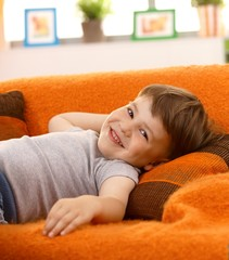 Cute little boy laughing on couch