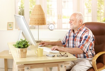 Senior man using computer at home