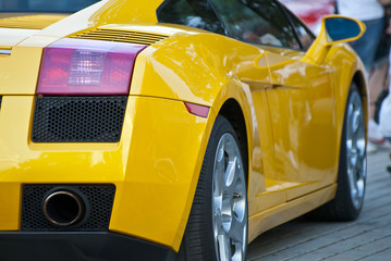Aluminium Prints Fast cars Yellow sportcar, half, back, on road