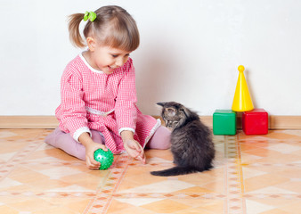 The girl plays with a kitten